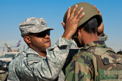 Train and Advise. US Army Combat Advisor Sergeant teaching a soldier in the Afghan National Army how to wear his helmet stock images