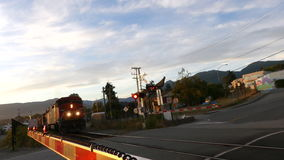 Train approaching red flashing lights. Blue sky small town station cargo train stock footage