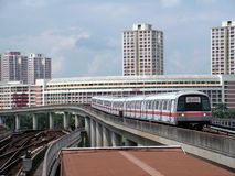 Train approaching station. A mass rapid transit ( MRT ) train approaching jurong east terminal on the island of singapore. In the background is government built Stock Photography