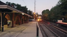 Train approaching station in evening (1 of 2). A view or scene of Transportion stock video