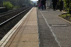 Train Approaching Station and People Waiting on Platform. Blurred train approaching Station and passengers waiting on platform in Wester Hailes Edinburgh stock photography