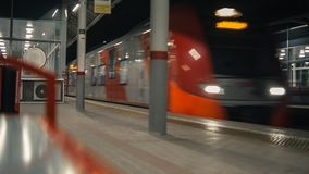Train arrival to station. At night. Shallow depth of field. Horizontal panning stock video
