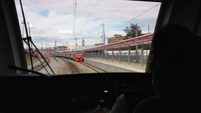 Train arrives to station with locomotive against sky. View from driver cabin with operator back on train arriving to railway station with locomotive against blue stock video