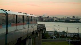 Train arriving at Haneda airport during sunrise.