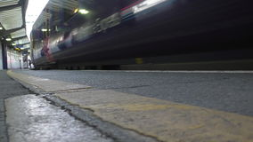 Train arriving at the platform low angle view. Low angle view of the passenger train coming toward camera at railway station platform stock video footage