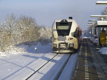 Train arriving at the railway station. Train coming into the railway station in the snow Stock Photo