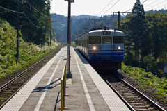 Train arriving at rural Japanese station. Royalty Free Stock Photo