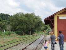 Train arriving in small train station, inland, on sunny day. Quiet Railway Station, with passengers waiting for the next arrival of a train with lights on Stock Images