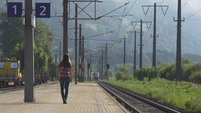 Train arriving to the station. Woman is waiting. Woman on railway station looking into the distance waiting for approaching train stock video footage