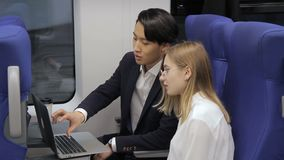 On train an Asian man shows a woman wearing glasses a laptop. Young male Korean advertises female client for new technologies for computer equipment in railway stock video footage