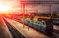 Train awaits passengers on peron in the rays of the sun Stock Images
