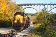 Train below bridge. An oncoming passenger train under a high arch bridge in a scenic area Royalty Free Stock Photo