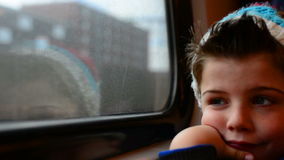 Train boy. Boy in a moving train with his reflection in the window stock footage