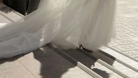 Train of the bride dresses down the stairs. Train of the bride dress descends the steps on a wedding day stock video