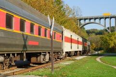 Train before bridge. A scenic passenger train nears a high arch bridge in a rural area Stock Photo