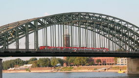 Train on Bridge in Cologne, Germany. Red regional train on Cologne Hohenzollern railway bridge across the Rhine river in Germany stock video footage