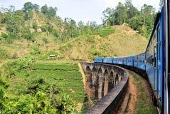 Train on bridge in hill country of Sri Lanka. A Train passing on a bridge in the hill country of Sri Lanka with its tea plantations close to Ella Stock Photo