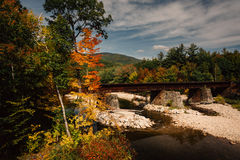 Train bridge over a river and autumn color near Bethel, Maine. Royalty Free Stock Photography