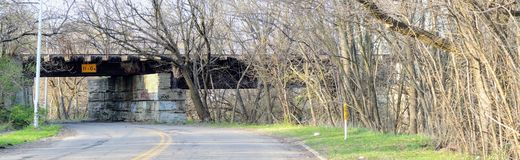 Train Bridge over urban side road graffiti, with row of trees in early spring in Indianapolis Indiana, United States. USA Stock Photos