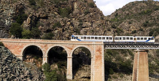 Train on the bridge through a precipice, Corsica. France Royalty Free Stock Images
