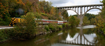 Train, Bridge and River. Brightly colored train traveling under a bridge.  The bridge is reflected in the water Stock Images