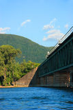Train bridge, river, mountain. Perspective of a train bridge over the Richelieu river in Mont St-Hilaire, Quebec, Canada with trees, sky, clouds and mountain in royalty free stock image