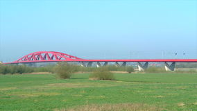 Train on a bridge. Yellow and blue passenger train of the Dutch National Railways is driving over the bridge over the river IJssel near the city of Zwolle stock video footage