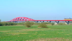 Train on a bridge. Yellow and blue passenger train of the Dutch National Railways is driving over the bridge over the river IJssel near the city of Zwolle stock video