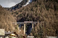 Train Bridge in Zermatt, Switzerland. Zermatt, Switzerrland - April 11, 2017: A red train crossing an arch bridge in Zermatt stock photos