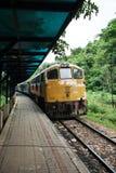 Train on Burma railway. Train at platform on Burma railway with tropical jungle in background royalty free stock image