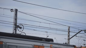 Train Cables And Train. This is footage of train cables while a train goes by. Only the roof or the top part of the train vagons can be seen stock video