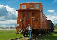 Train Caboose. A train caboose shot on a partly cloudy day along with a young man to show the size of it Royalty Free Stock Image