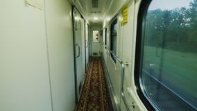 In the train car, a long corridor with a door in the compartment. Steadicam shot. In the train car, a long corridor with a door in the compartment stock footage