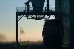 Train car rests by an elevator on a foggy autumn morning, waiting for the day to begin. Silhouette scene. Silhouette scene of train car by an elevator on the Stock Image