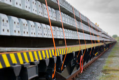 Train cargo wagons. Freight train cargo wagons loaded with concrete sleepers and shallow DOF Stock Images
