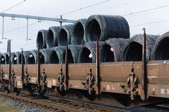 Train cargo wagons. Row of train cargo wagons with rolls of steel wire Stock Photo
