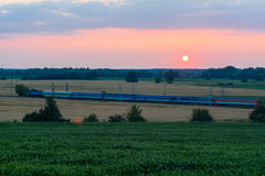 The train, with carriages on the train tracks at sunset in the countryside Stock Photos