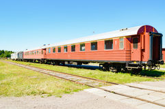 Train cars. Line of passenger train cars standing on railroad track. Blue sky above and green grass cover the ground beside the cars. Cars are mostly red. No Royalty Free Stock Photography