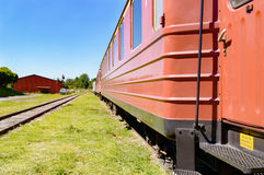 Train cars. Line of passenger train cars standing on railroad track. Blue sky above and green grass cover the ground beside the cars. Cars are mostly red. No Stock Images