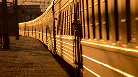 Train cars traveling about empty platform. Sunset, cars reflect sunlight sunset stock footage