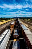 Train cars vertical down a track overlooking mountain range. Train cars vertical down a track overlooking mountain range, beautiful sky with streaking clouds stock image