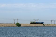 Train on causeway line at Kakhovka Water Reservoir, Ukraine.  stock photos