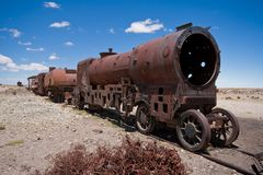 Train cemetery. Graveyard of rusty old steam trains in middle of Bolivian desert near Uyuni Royalty Free Stock Images