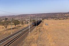 Train Coaches Dry Landscape. Railway train coaches travel through dry season rural landscape Stock Photo