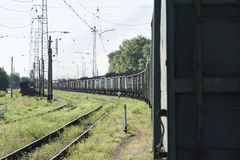 Train with coking coal cars on the background of the coke plant. Stock Photos