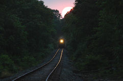 Train coming from setting sun Stock Images
