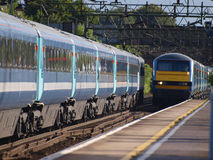Train coming into station. Two trains passing at speed through station Stock Photo