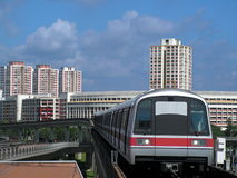 Train coming into station. Background is the apartment buildings that are the homes of lower to middle class singaporeans. trains typically have six carriages Royalty Free Stock Image