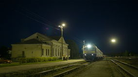 Train coming to rural station. Passenger train making a stopover at a small rural station at night, engine driver leaving cabin to check the train stock video footage