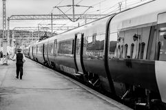 Train and conductor - black white. Train at Halden railway station with conductor checks before departure Stock Photography